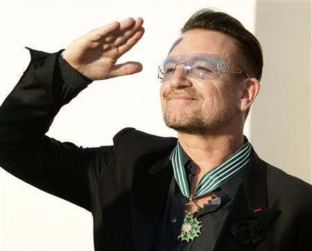 Musician Bono, lead singer of the band U2, reacts after being awarded as Commandeur des Arts et lettres (Commander in the Order of Arts and Letters) by French Culture Minister Aurelie Filippetti during a ceremony at the ministry in Paris July 16, 2013. REUTERS/Charles Platiau