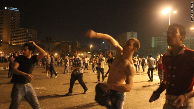 Protesters throw stones at riot police during clashes in Tahrir Square in Cairo, Egypt, during the early hours of June 29.