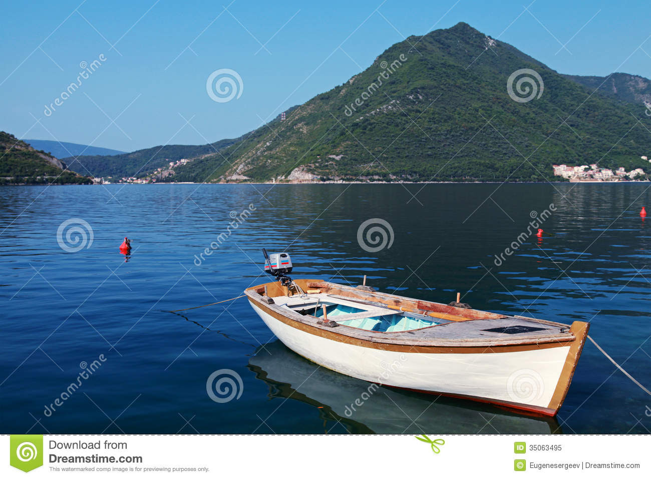 White wooden fishing boat floats moored in Perast town, Adriatic sea