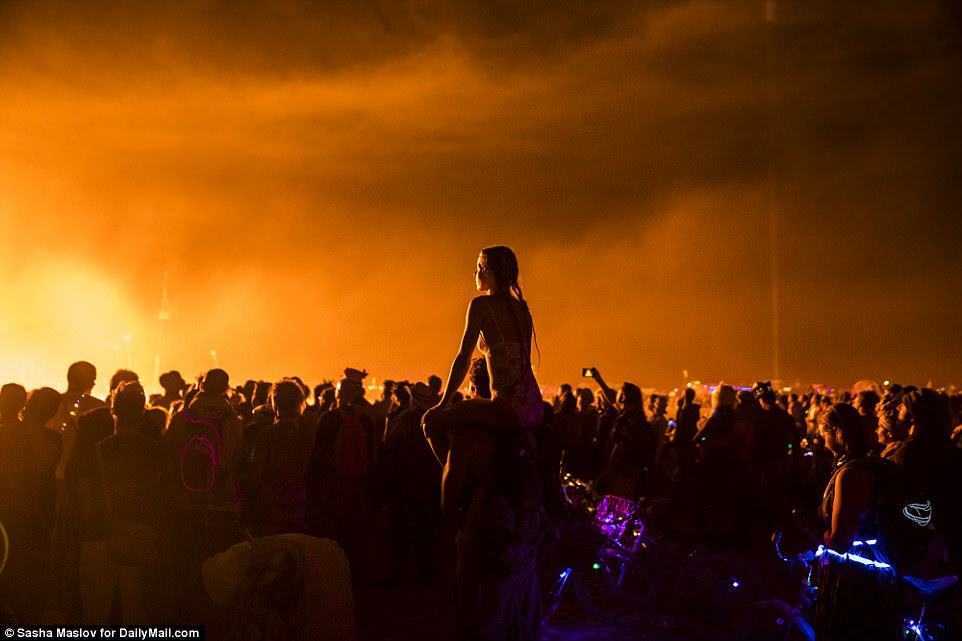 A girl sits on the shoulders of her male friend watching the stunning lights show as thousands of revellers watch on it awe