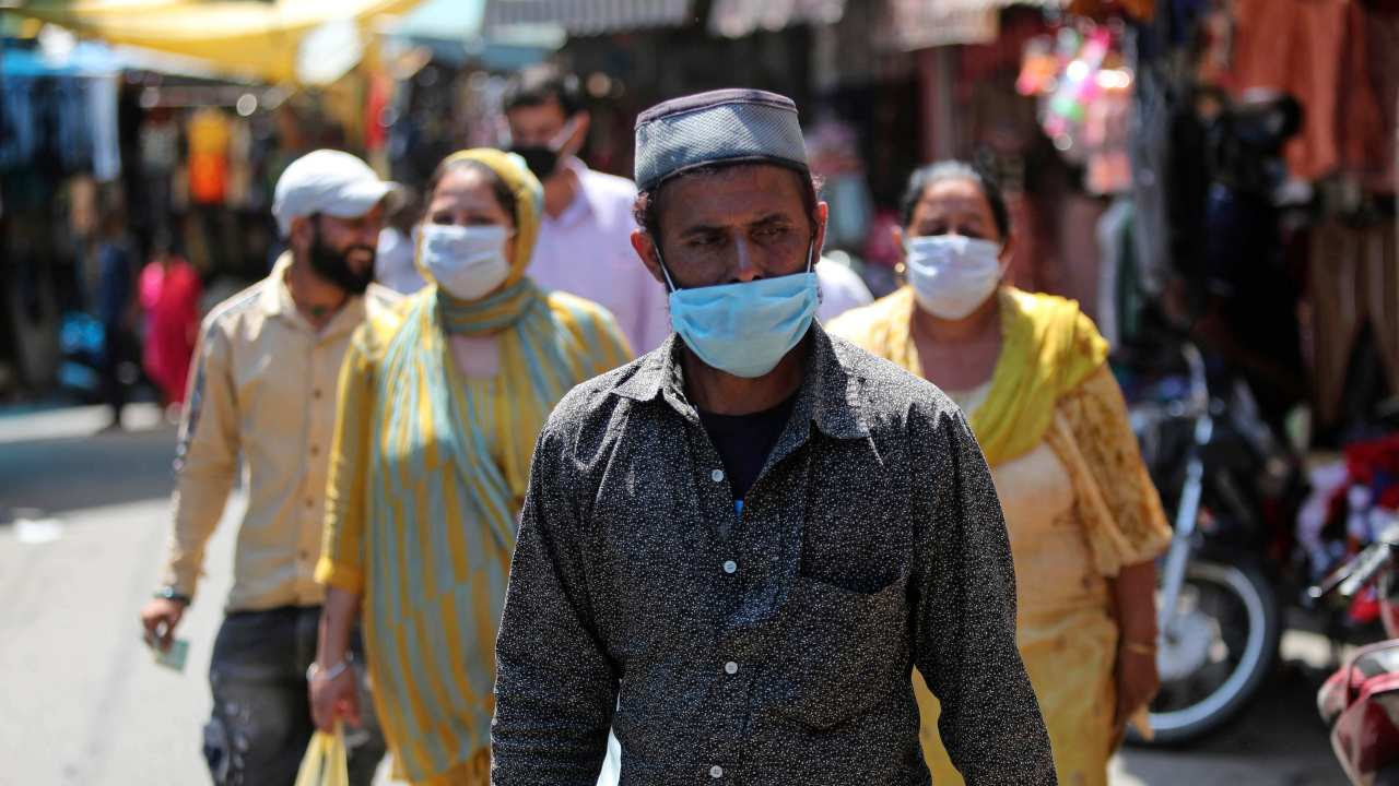 Commuters wearing a mask walk in a Jammu market, as COVID-19 continues to wreak havoc across the board.
