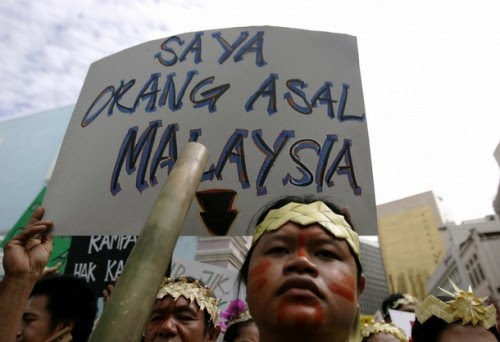"""An indigenous Malaysian holds a placard saying """"I am an original inhabitant of Malaysia"""" during a demonstration to call for the government to implement the individual and collective rights of indigenous people, in Kuala Lumpur September 13, 2008."""