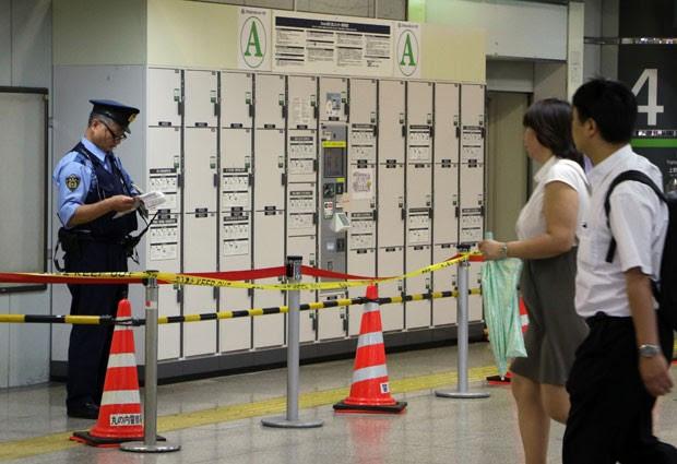 Policial é visto em guarda-volumes em estação de Tóquio nesta segunda-feira (1º). O corpo de uma mulher foi encontrado em uma mala deixada em um armário de uma estação de trem da cidade há um mês (Foto: Yoshikazu Tsuno/AFP)