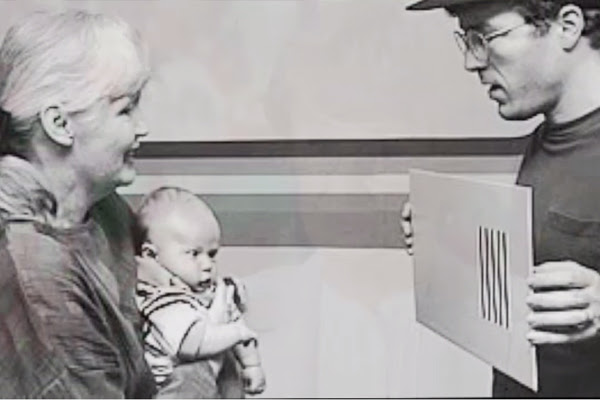 Davida Teller is on the left holding her grandson while the baby is being shown a Teller acuity card by his father.