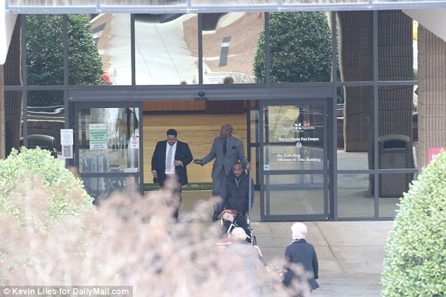 In a series of pictures taken from outside the hospital's main entrance, Nick Gordon comes out of the hospital and paces up and down, before chatting with acquaintances. He then goes back inside and emerges pushing Danyela in a wheelchair
