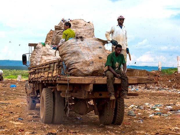 Os catadores trabalham sem equipamento de proteção e correm dos caminhões e tratores para não serem atropelados. Acima, Catadores pegam carona de forma irregular em um caminhão de lixo.  (Foto: Paula Fróes)