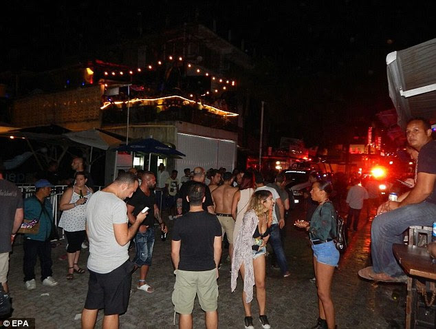 People wait outside a club where a shooting took place in Playa del Carmen early Monday morning