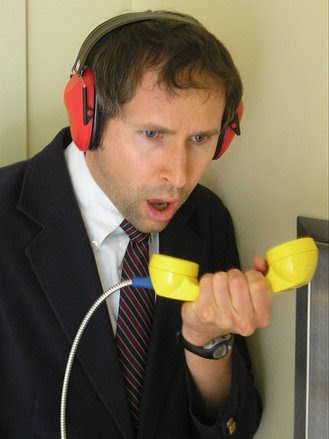 Man attempting to make a call using corded phone while wearing headphones.