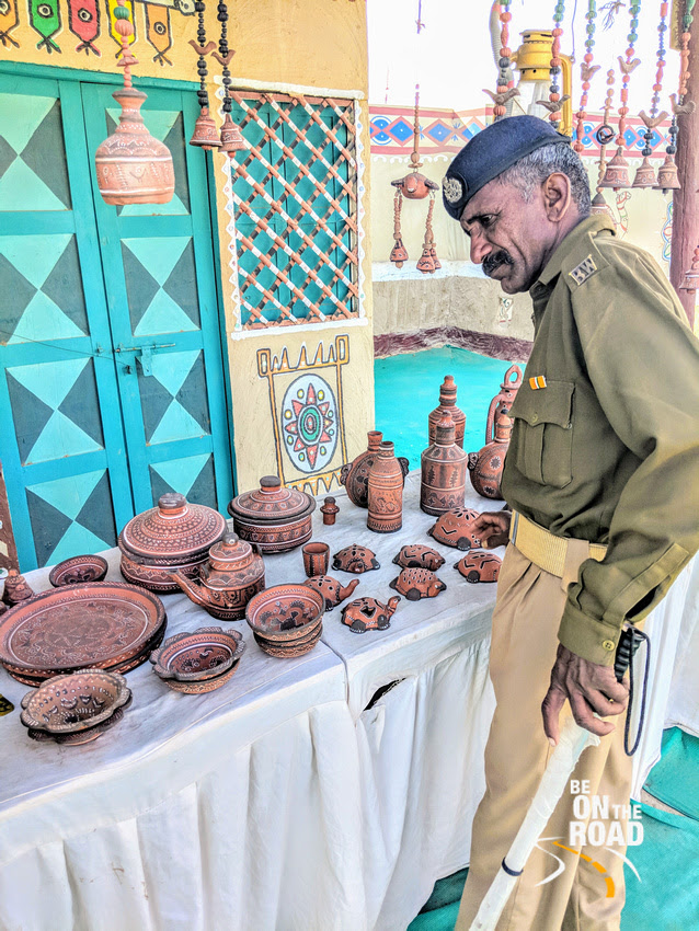 Local cop admires the pottery of Kutch showcased at Rann Utsav Tent city