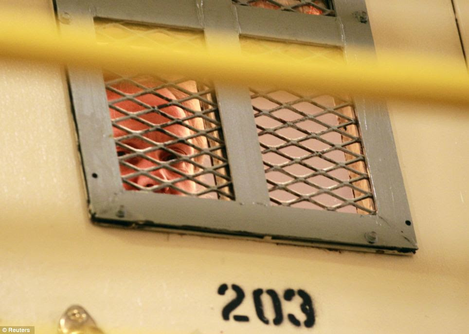 An inmate looks out from his cell in Chino, California - many such prisons have two or three detainees living in a single room designed for one