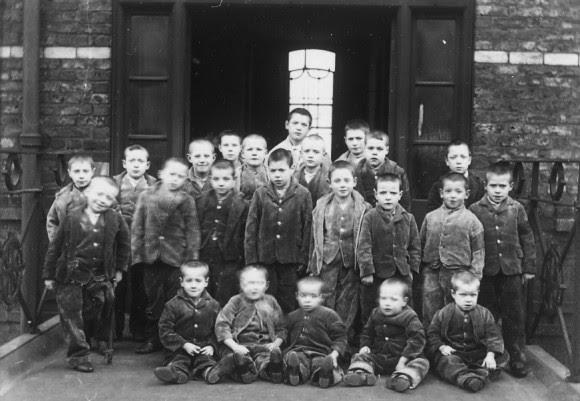 Fotografía de un grupo de niños trabajadores de un taller, c. 1895