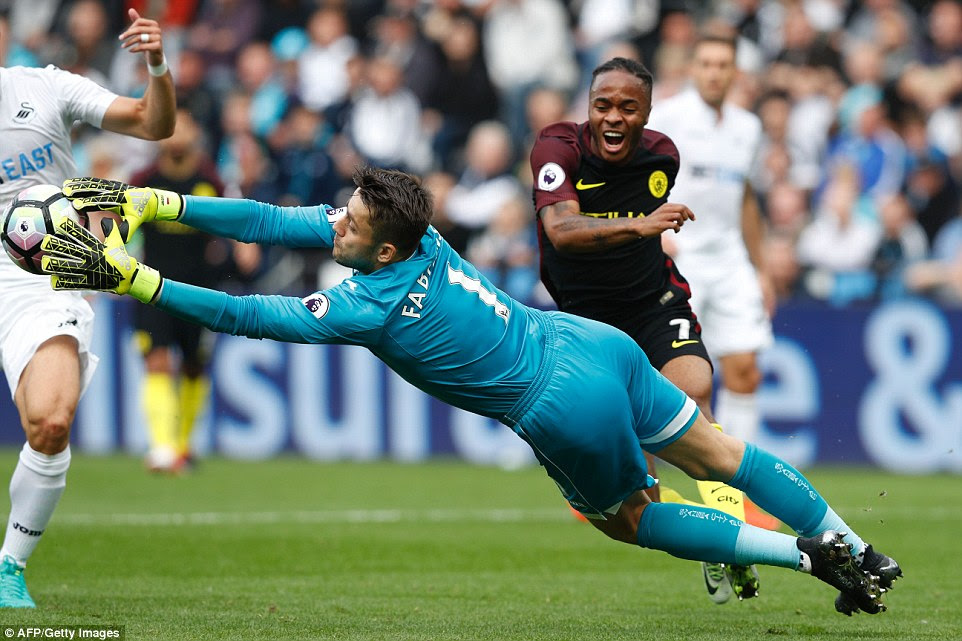 Fabianski has to dive full length to claim the ball inside his area as he comes under pressure from Raheem Sterling