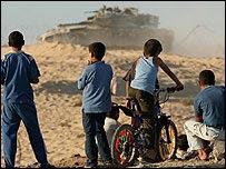 Niños palestinos observan un tanque israelí junto al asentamiento de Neve Dekalim, en Gaza
