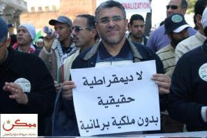 "El Mostafa Ramid before he became the Current minister of Justice and Liberties holding a signboard which says: ""No Real Democracy  without a Parliamentary Monarchy"""