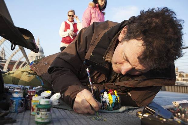 Ben Wilson durante pinturas na ponte Millennium, em Londres, na terça-feira (28). (Foto: Finbarr O'Reilly/Reuters)