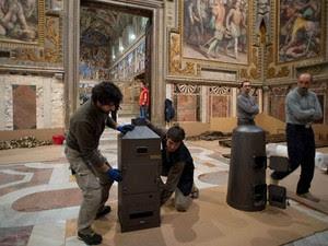 Funcionários instalam os fornos onde serão quimados os votos do conclave (Foto: Osservatore Romano/Reuters)
