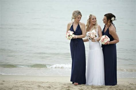 Navy bridesmaid dresses with peach and pink flowers. Beach