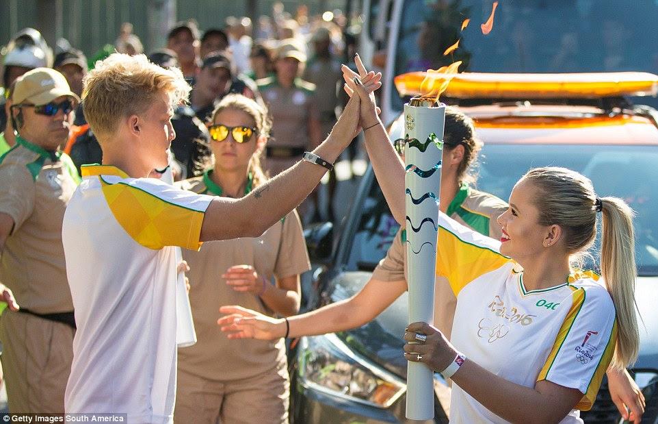 Coca-Cola da tocha olímpica ao Portador (e irmão mais velho) Cody Simpson mãos a tocha para sua irmã mais nova Alli antes de sua tocha olímpica passar por Rio de Janeiro