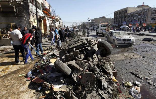 Moradores observam destroços de carro-bomba nesta terça-feira (19) em Bagdá, capital do Iraque (Foto: AFP)