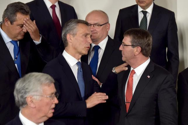 NATO Secretary General Jens Stoltenberg (C) and U.S. Secretary of Defense Ash Carter (R) chat after a family photo, following a meeting of the North Atlantic Council (NAC)  in Defense Ministers session at the NATO headquarters in Brussels, Belgium June 24, 2015. NATO defence ministers met in Brussels on Wednesday, where they were expected to discuss security in the eastern European region as well as budgetary matters. REUTERS/Eric Vidal