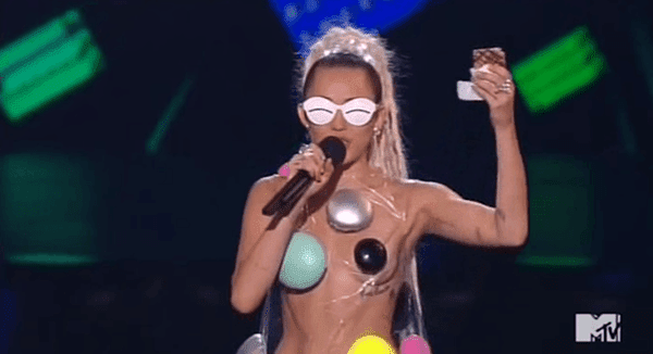 Vemos, então, Miley vestida desse jeito, com óculos que nos lembram como escravos MK são completamente cegos para o que está acontecendo com eles.  Ela está segurando um bolo atado com drogas dadas a ela por algum gajo rapper.  Seus pops deve ser muito orgulho dela.