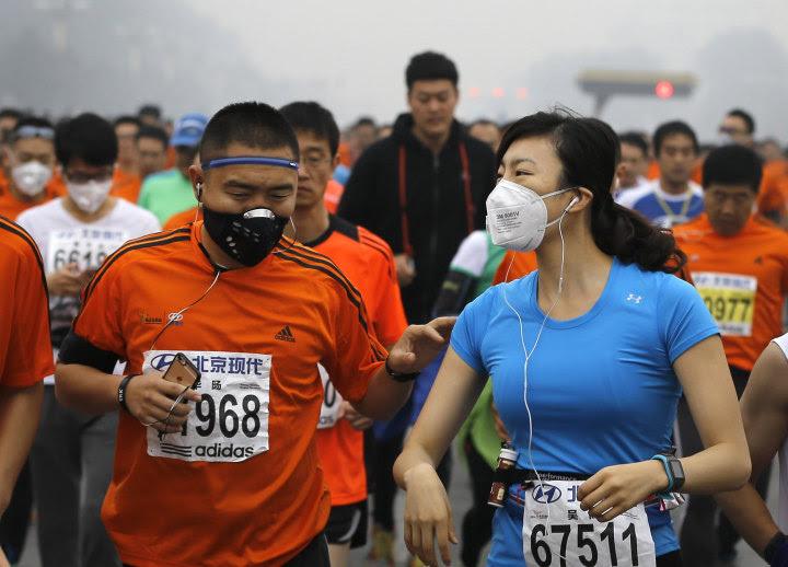 Image: Runners jog past Tiananmen Gate shrouded in haze