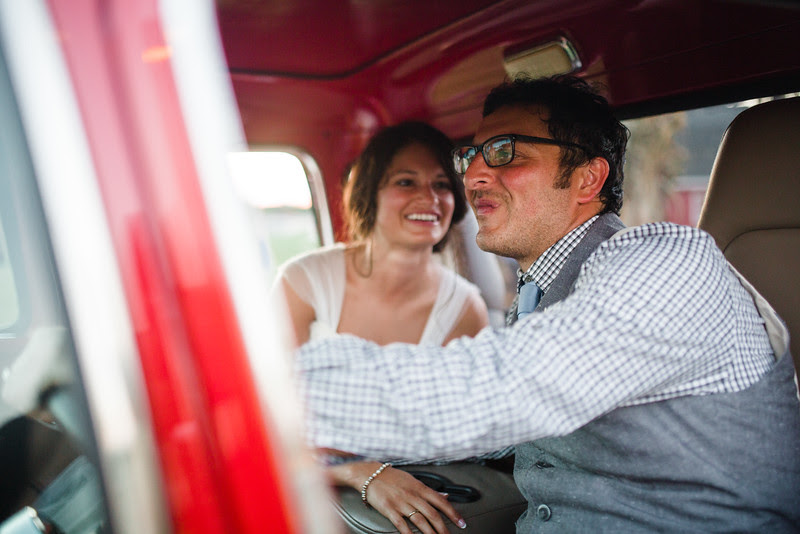 The bride and groom take their photos by a vintage red truck at Busy Barns Adventure farms before a wedding at Busy Barns Adventure Farms in Fort Atkinson Wisconsin about 30 minutes east of Madison and an hour north of Chicago. Photo by Mindy Joy Photography.