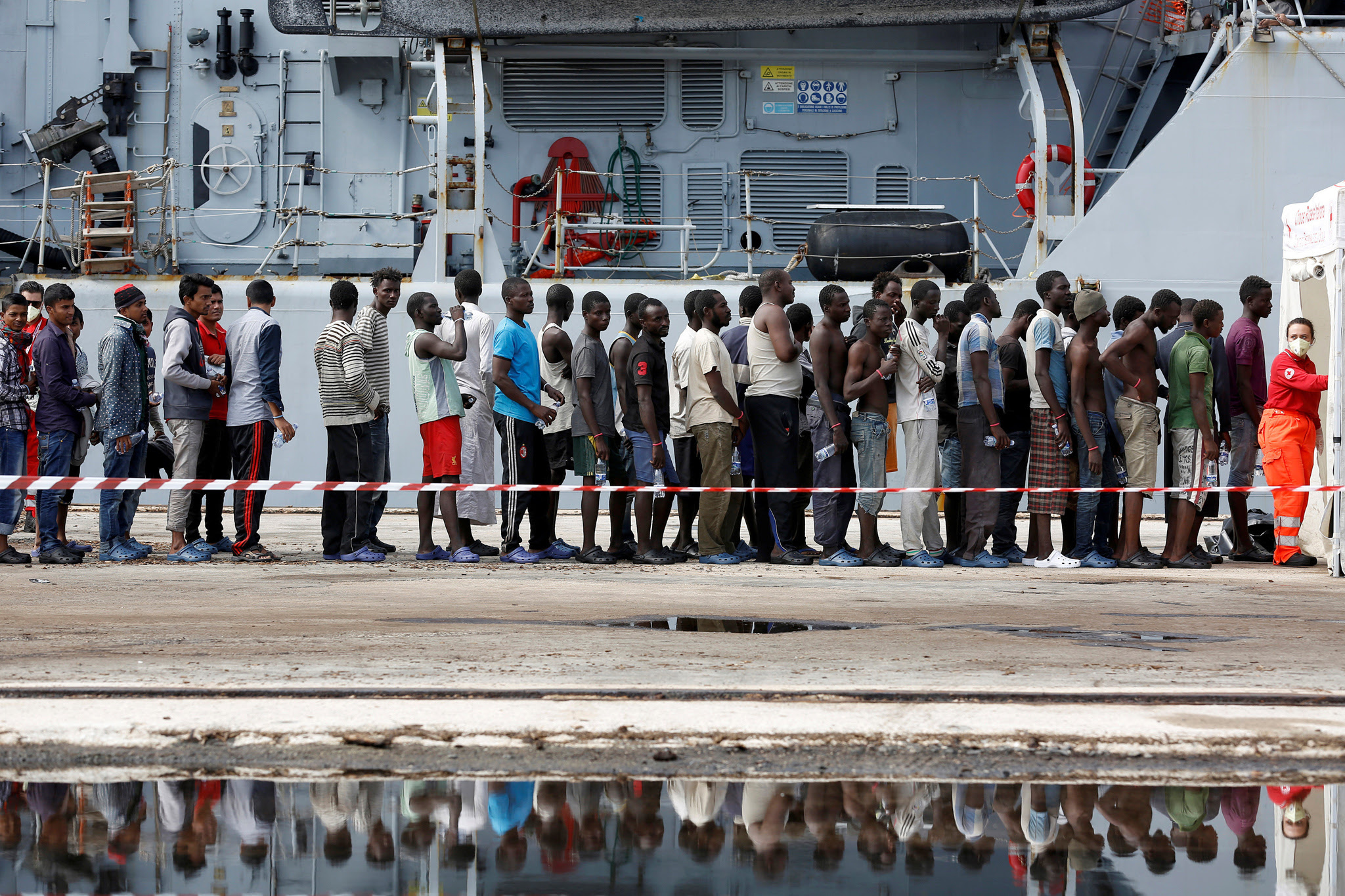Migrants stand in line after disembarking from the Italian Navy vessel Bersagliare at the Sicilian port of Augusta, Italy