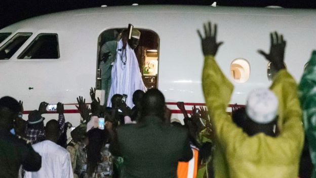 Former president Yaya Jammeh (C,up), the Gambia's leader for 22 years, waves from the plane as he leaves the country on 21 January 2017 in Banjul
