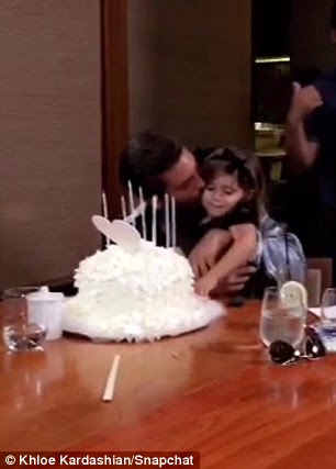 Daddy's little girl: Scott planted a sweet kiss on his little girl who wore a black frock with a cute black bow in her hair