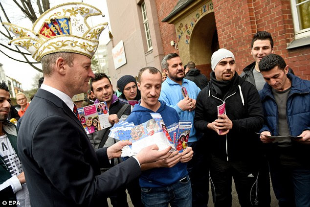 Warning: Bonn carnival chief Christoph Arnold hands out a leaflet to refugees in Bonn, Germany, warning them about the rules for next week's Carnival - including not sexually assaulting women or urinating in public
