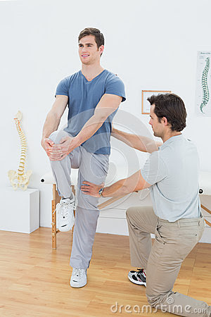 Male Therapist Assisting Young Man With Stretching ...