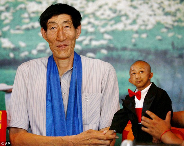 Size matters: The world's tallest man, Bao Xishun, who stands 7.9 feet, shakes hands with He Ping Ping - who died last year - the smallest man in the world at 28.8 inches prior to Mr Magar