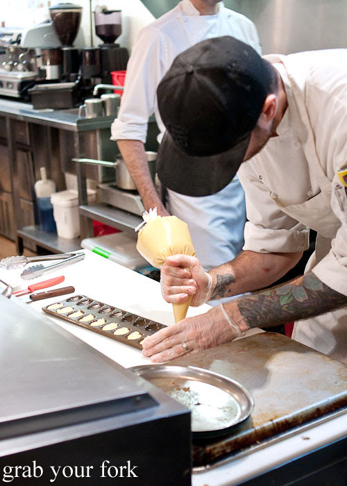 pastry chef piping madeleines at dominique ansel bakery nyc new york