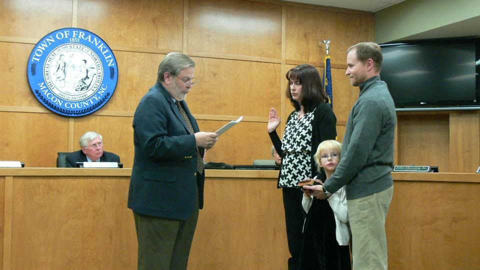 Vic Perry swears in Patti Halyburton Abel as Alderman while her family looks on