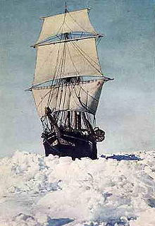 Frontal view of ship with sails all set, moving through thick sea ice
