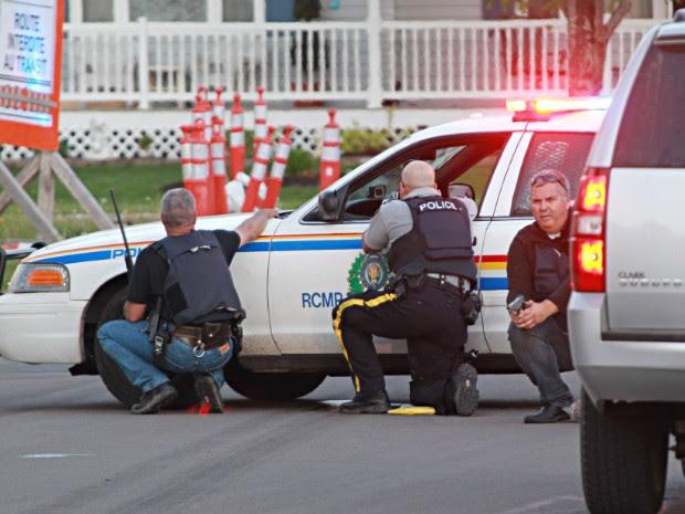 Agentes da polícia se escondem atrás de seus veículos em busca do atirador que teria matado policiais no Canadá (Foto: AP Photo/Moncton Times & Transcript, Ron Ward via The Canadian Press)
