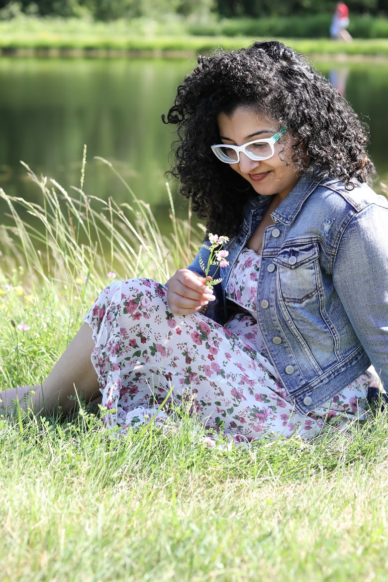 For Bell Let's Talk, Shahzadi Devje Desi~licious RD sitting on grass holding and looking at a flower