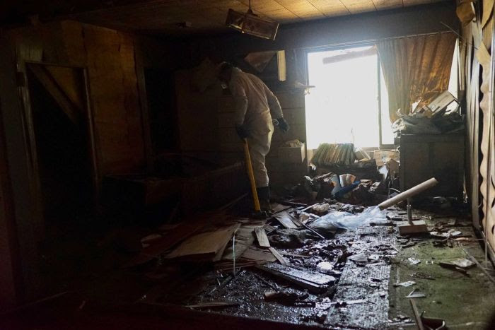 A person walks among damaged property inside a home that was f   looded.