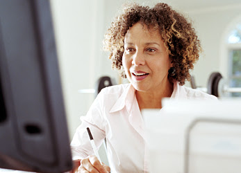 Woman looking at computer while writing on paper.