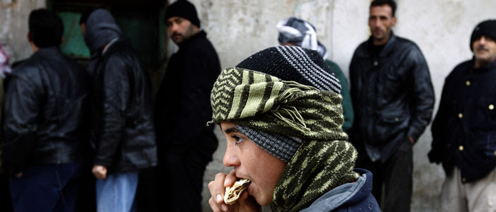 A boy eats bread as others wait in front of a bakery shop during winter in Al Qusayr