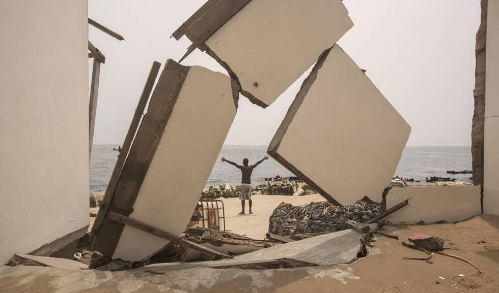 El último hombre que vive en la isla ghanesa de Kpogbor, ante la defensa que ha construido para proteger lo que queda de su casa.
