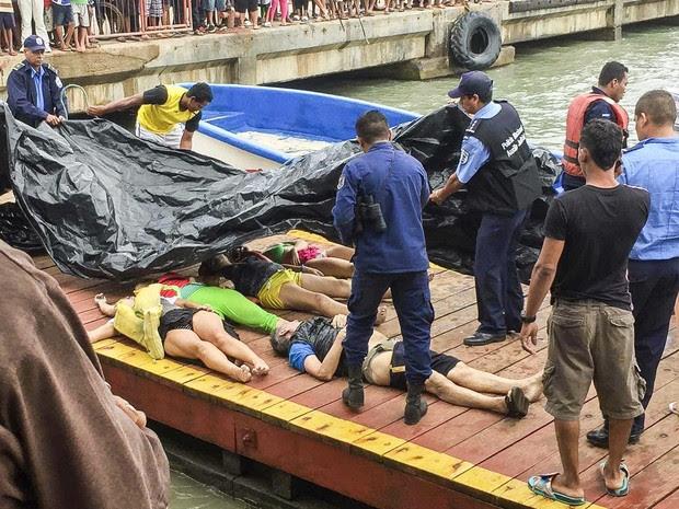 Membros da Força Naval e da polícia da Nicaraguá recebem os corpos dos mortos no naufrágio (Foto: STF/AFP)