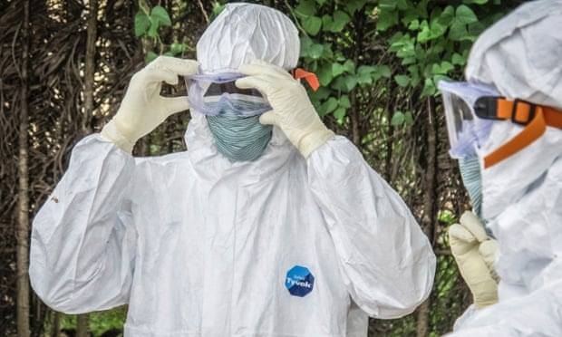 Health workers wear protective gears before entering the house of a person suspected to have died of Ebola virus in Port loko Community situated on the outskirts of Freetown, Sierra Leone, Tuesday, Oct. 21, 2014.