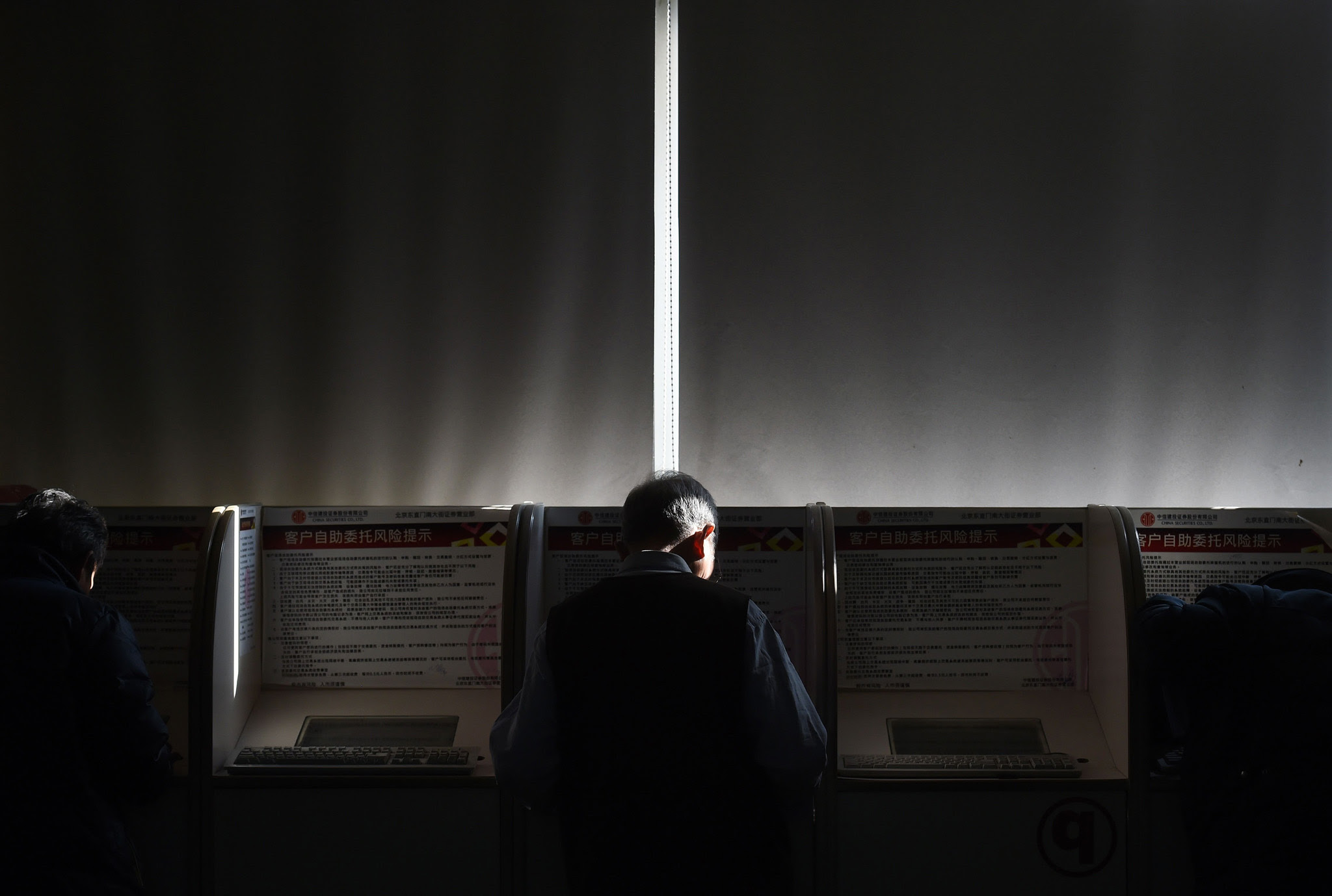 An investor checks stock prices at a terminal in a securities company in Beijing