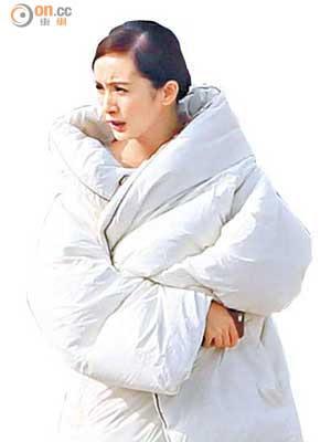 楊冪穿上有如棉胎的羽絨,捱冷在流浮山露出香肩拍廣告,發現記者後即皺眉頭。