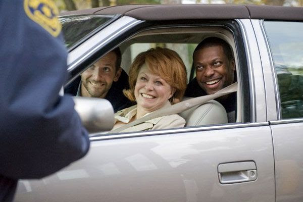 Dolores speaks to a police officer after picking Pat and Danny (Chris Tucker) up from a mental institution in SILVER LININGS PLAYBOOK.