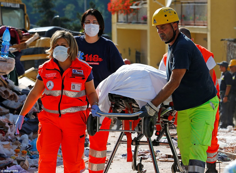 A body is carried away on a stretcher as rescuers continue the hunt for survivors of the deadly earthquake