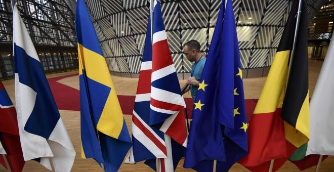 Un empleado limpia junto a las banderas europeas, dispuestas para la última cumbre de los lideres de la UE, en Bruselas, el pasado 9 de marzo. REUTERS/Dylan Martinez