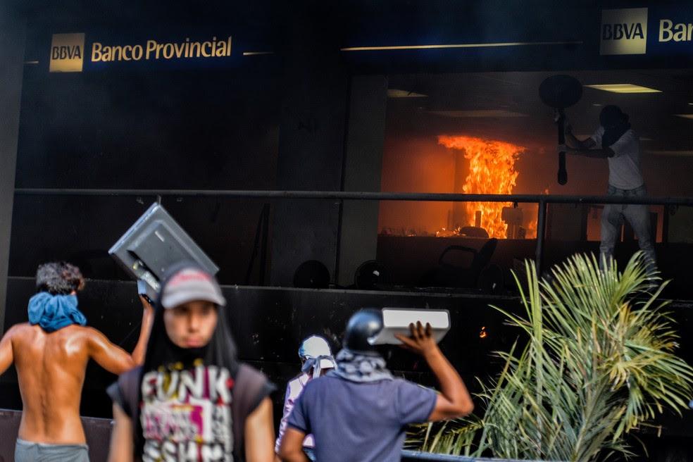 Opositores incendiam agência bancária que fica em prédio administrativo do Tribunal Superior de Justiça da Venezuela nesta segunda-feira (12) em Caracas (Foto: LUIS ROBAYO / AFP )